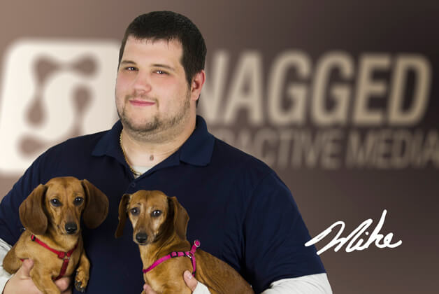 Headshot of Mike Lafrenière holding his dogs with his signature