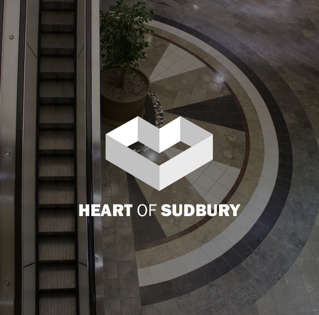 Heart of Sudbury logo over a photo of the escalator inside the Rainbow Mall